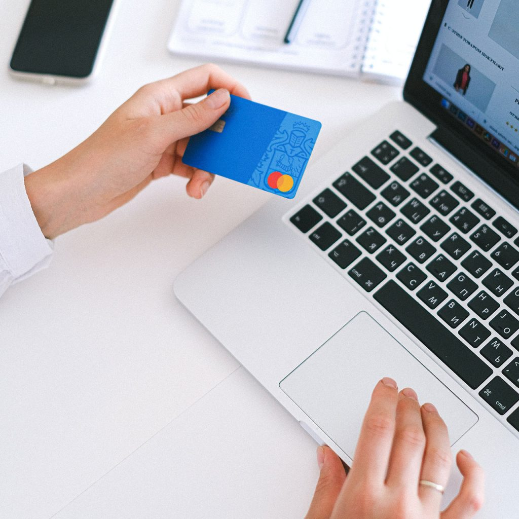 Client holding credit card in front of laptop Alter Image Digital Media web designers ecommerce developers Midrand Johannesburg South Africa