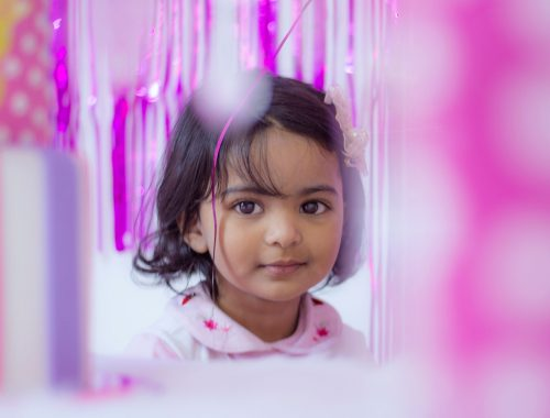 Girl looking through pink party decorations